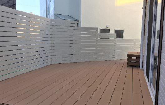 白いフェンスと変形地対応のウッドデッキ